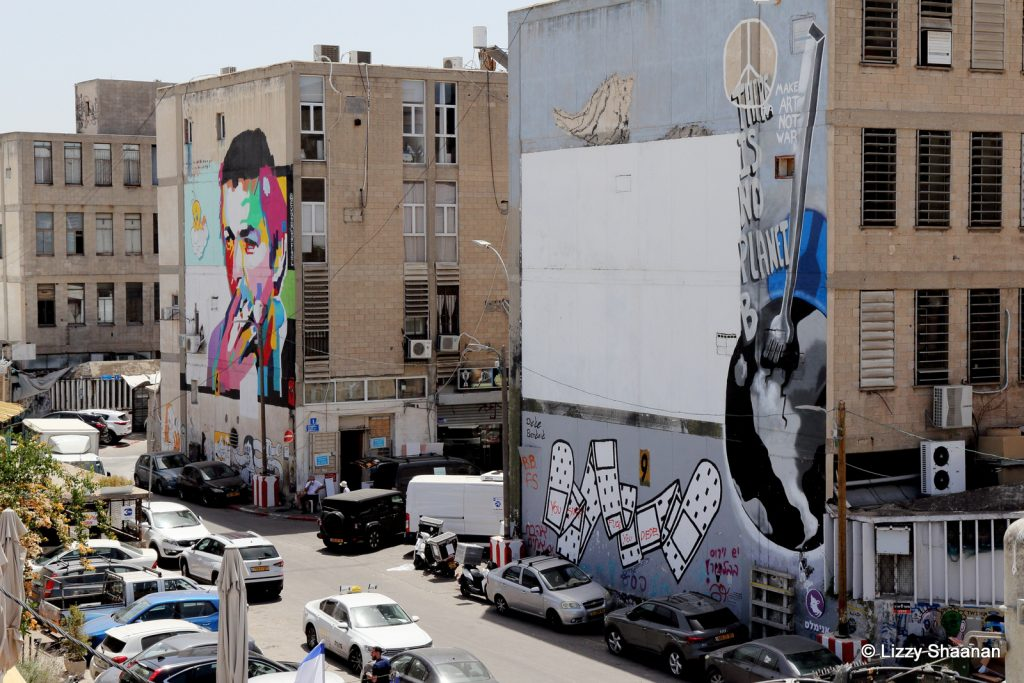 פלסטרים של אמן הרחוב דדה ודיוקן של אריק אינשטין מצויר על הבנין שלידו